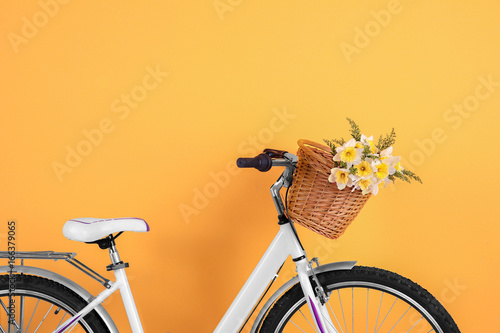 Photo sur Toile Velo Bicycle with basket of beautiful flowers on color background