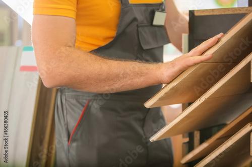 Fototapety, obrazy: Carpenter choosing laminate samples in hardware store