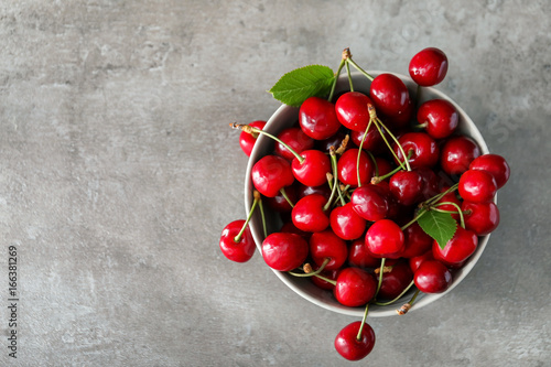 Bowl with fresh ripe cherries on grey background