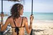 Woman in a bikini sitting at the swing looking at the sea