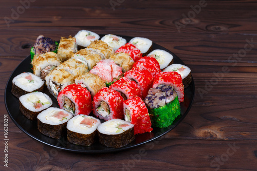 Foto  Colorful set of japanese sushi maki rolls with salmon, tuna and avocado served o