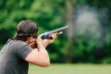 Man Firing His Shotgun While Skeet Shooting