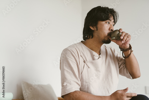 Man wearing traditional Chinese cloth drinking tea