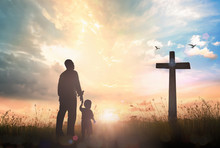 Resurrection Of Easter Sunday Concept: Silhouette Father And Son Looking For The Cross On Meadow Sunrise Background.