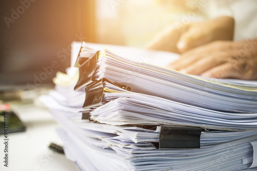 Fototapeta Businessman hands searching information in Stack of papers files on work in office, business report paper or piles of unfinished documents achieves with clips on offices Business concept obraz