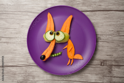 Fox made of fresh vegetables on plate and board