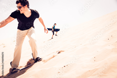 Photo  Tourist Sandboarding In The Desert