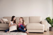 canvas print picture - Two happy beautiful girlfriends in casual clothes and cellphones in hands sitting on carpet on floor in living room. Female friends relaxing and spending time together, browsing and chatting online