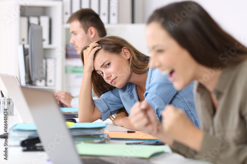 Canvas Print Worried worker beside successful one