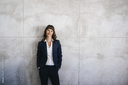 Businesswoman leaning against office wall with hands in pockets