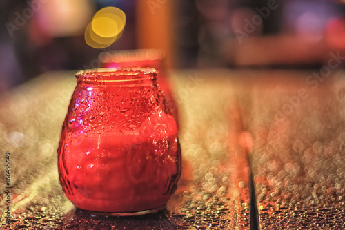 Photo  Read painted glass lantern on the wooden table with water drops