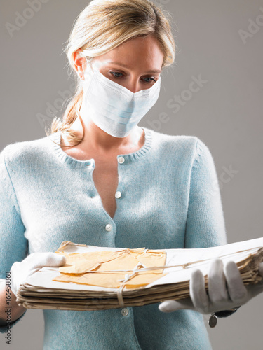 Photo Woman with mask, holding precious files