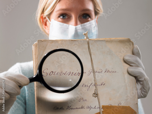 Woman with magnifying glass showing file Wallpaper Mural