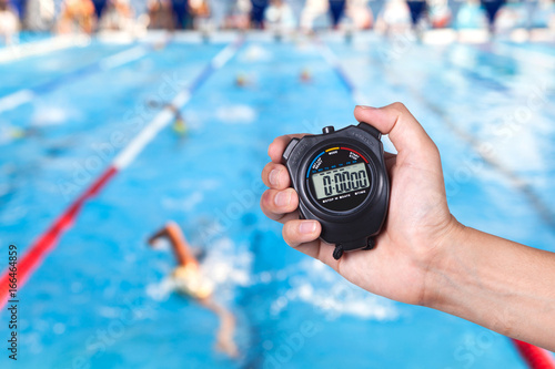 Fototapeta Stopwatch holding on hand with competitions of swimming background. obraz