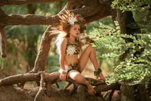 Beautiful Little Girl In Image Of Nymph Dryad Sits On Tree Roots In Magical Forest .