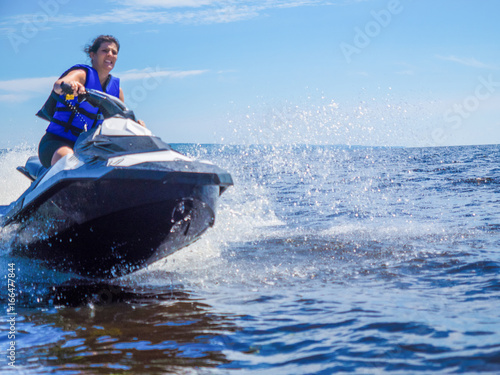 Poster Nautique motorise Woman riding jet ski on lake in summer