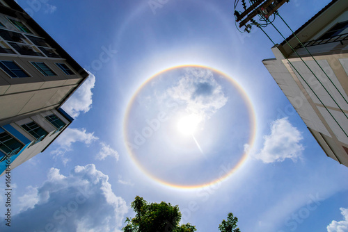 building and sun corona rainbow clouds and blue sky background , Circumscribed halo