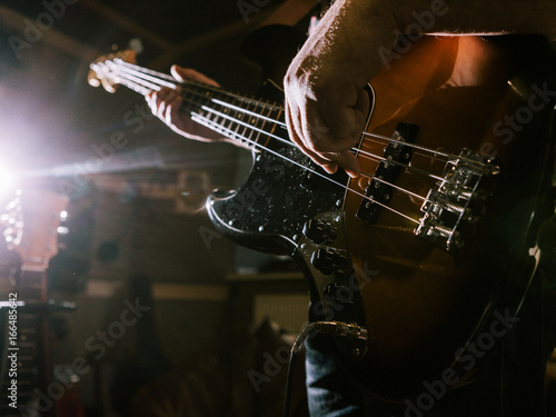 Spoed Foto op Canvas Grill / Barbecue Playing bass guitar strings closeup. Unrecognizable guitarist, music recording studio, dark atmosphere with back light