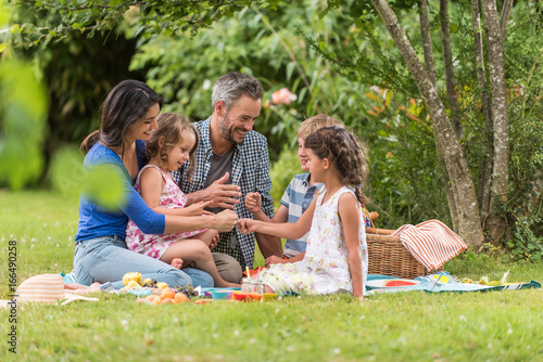 Cheerful family sitting on the grass during un picnic in a park