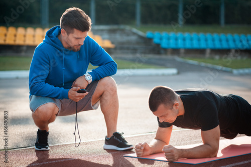 Photo morning plank exercises with personal coach with stopwatch;