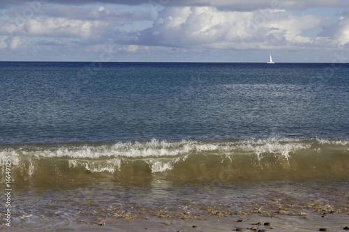 Fototapeten Natur Mar azul com pequeno veleiro ao longe