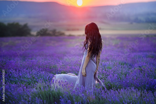 Foto op Canvas Snoeien Beautiful woman in a field of lavender on sunset. Woman in amazing dress walk on the lavender field.