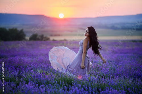 Poster Prune Beautiful woman in a field of lavender on sunset. Woman in amazing dress walk on the lavender field.