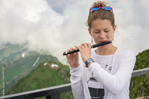 Fotografie, Obraz  Девушка играет на флейте на фоне гор и облаков