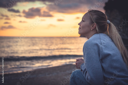 Obraz Pensive lonely smiling woman looking with hope into horizon during sunset at beach - fototapety do salonu