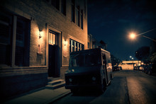 An Armed Security Truck Parked In A Dark City Street At Night Next To A Building Entrance.