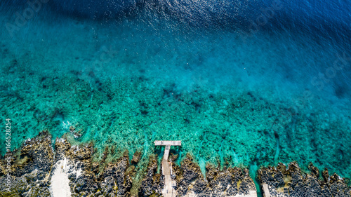 Aerial view of a small dock leading out over clear water onto a tropical coral reef