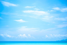 Beautiful White Clouds On Blue Sky Over Calm Sea With Sunlight Reflection, Tranquil Sea Harmony Of Calm Water Surface. Vibrant Sea With Clouds On Horizon