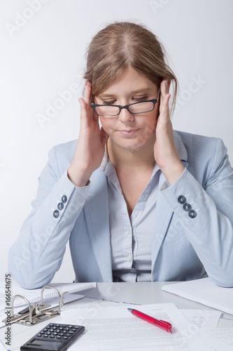 Fotografie, Obraz  Junge Frau sitzt verzweifelt am Schreibtisch mit Papierkram
