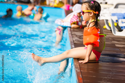 Little girl playing in outdoor swimming pool jumping into water on