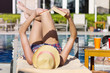 Beautiful young woman relaxing on a pool with book.Summer holiday