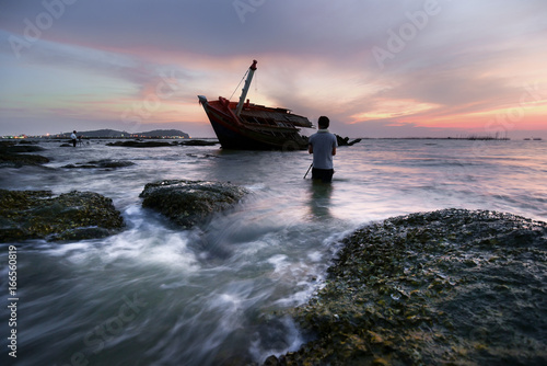 An old shipwreck or abandoned shipwreck.,Wrecked boat abandoned stand on beach or Shipwrecked off the coast of Thailand.