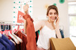 Nice girl in white top standing near sale clothes rack with T-shirt in hand and happily looking on it in boutique. Portrait of lady talking on cellphone with shopping bags in hand in clothes store