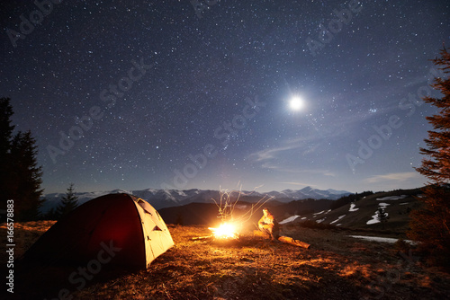 Male Hiker Have A Rest In His Camp Near The Forest At Night Man Sitting Campfire And Tent Under Beautiful Sky Full Of Stars Moon