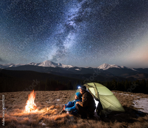 Spoed Fotobehang Kamperen Romantic couple tourists enjoying in the camping at night, having a rest near campfire and green tent under beautiful night sky full of stars and milky way. On the background snow-covered mountains