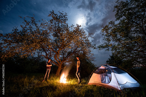 Fototapeta Romantic couple tourists standing at a campfire near tent under trees and night sky with the moon. Night camping obraz na płótnie