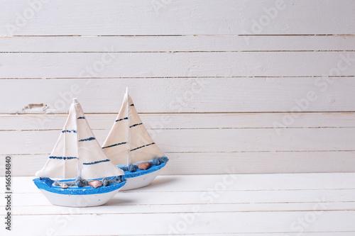 Fotografie, Obraz  Decorative wooden toys  sailing boats on  white wooden background