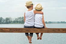 Two Brothers In A Straw Hats Sitting On The Pier And Looking At The Lake.Summer Vacation
