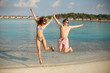 Happy young couple have fun and relax on the beach. Man and woman jump holding hands and smiling. Bungalows of spa resort, palms, and blue sea on background. Family travel concept