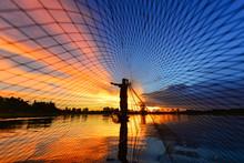 Silhouette Of Fishermen Casting His Fishing Net, Thailand