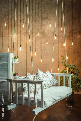 Zdjęcie XXL Projektowanie wnętrz. Przytulny pokój z białą wiszącą ławką.