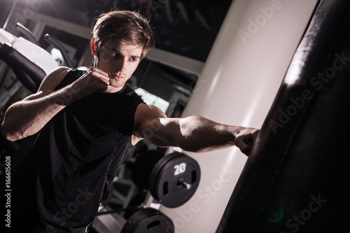 Concentrated muscular kickbox fighter exercising with punch bag on white in gym Wallpaper Mural