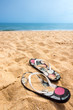 A pair och sandy flip flops on a beautiful summer beach with blue horizon and no people.