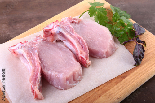 Keuken foto achterwand Vlees Raw pork steak with spices Leaves of coriander on wooden cutting board. Ready for cooking.