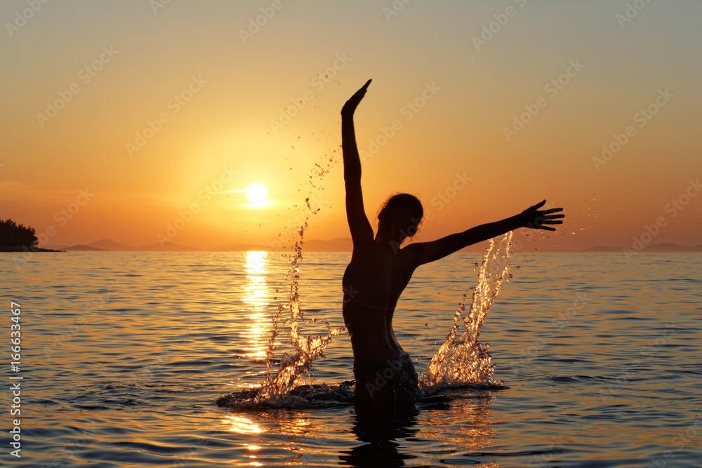 Obraz Sylwetka kobiety w wodzie na tle zachodzącego słońca fototapeta, plakat