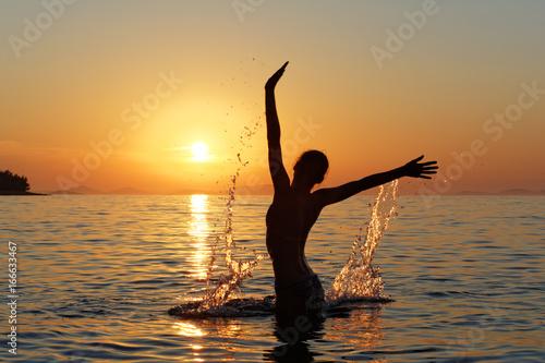Fototapeta Sylwetka kobiety w wodzie na tle zachodzącego słońca obraz
